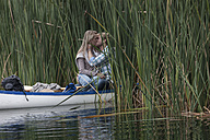 Young couple kissing in a canoe on a lake - ZEF005800
