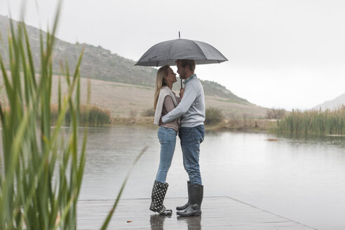 Couple standing in the rain on wooden boardwalk with umbrella - ZEF006217