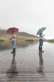 Couple standing in the rain on wooden boardwalk with umbrellas - ZEF006221