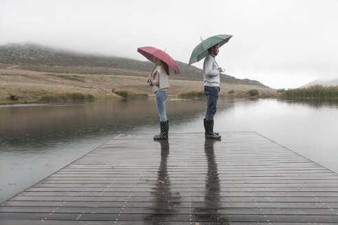 Couple standing in the rain on wooden boardwalk with umbrellas - ZEF006222