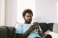 Young man at home reading messages on smart phone - EBSF000683