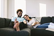 Young couple lying on couch looking at smart phone - EBSF000684