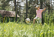 Boy playing with football in meadow - DEGF000440