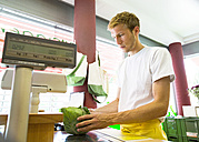 Male shop assistant in wholefood shop, weighing gabbage - SGF001661