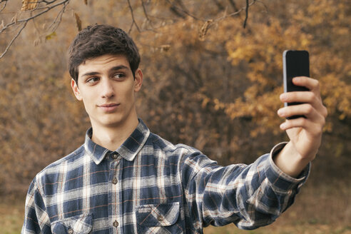 Portrait of young man taking a selfie with smartphone in a park - BZF000160