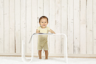 Smiling baby girl standing behind modern side table - DRF001648