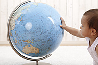 Baby girl looking at a globe - DR001656