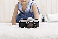 Camera lying on carpet while baby girl crawling in the background - DRF001659