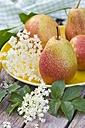 Pears with water drops on plate, elderflowers on wood - YFF000437