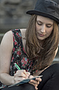 Young woman writing a postcard - PAF001423