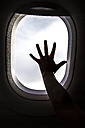 Silhouette of girl's hand on window on board of an airplane - JFEF000675