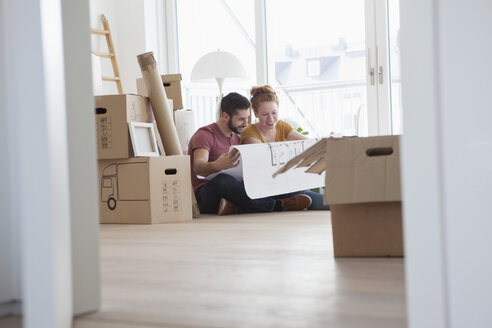 Young couple in new flat with cardboard boxes holding ground plan - RBF002861