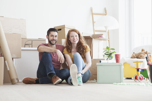 Young couple in new flat with cardboard boxes - RBF002780