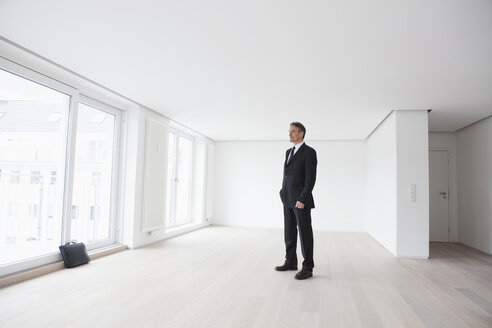 Estate agent standing in empty apartement - RBF002799
