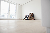 Young couple sitting on floor of their new flat - RBF002813