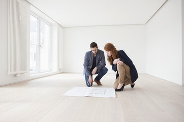Young couple sitting on floor of their new flat, looking at ground plan - RBF002816