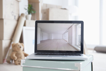 Laptop with picture of empty room in front of piled cardboard boxes - RBF002819