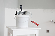 Paint bucket and roll on white table - RBF002823