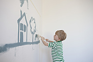 Little boy painting house and tree on wall of his new room - RBF002826