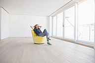 Young woman sitting on yellow armchair in her empty living room - RBF002752