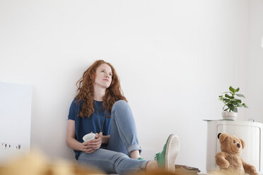 Daydreaming young woman sitting on floor of her living room - RBF002831