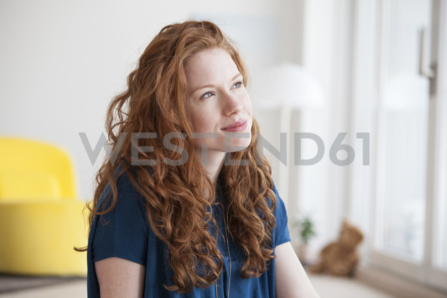 Portrait of daydreaming young woman at home - RBF002761 - Rainer Berg/Westend61