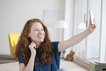 Young woman sitting in her living room taking a selfie with smartphone - RBF002764