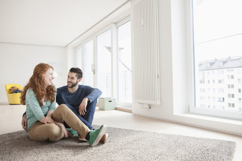Young couple sitting on the floor of living room - RBF002835