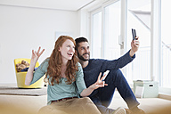 Smiling young couple taking a selfie with smartphone in the living room - RBF002765