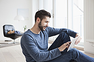 Young man sitting on the floor of living room using mini tablet - RBF002830
