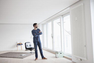 Young man standing in his living room looking through window - RBF002842