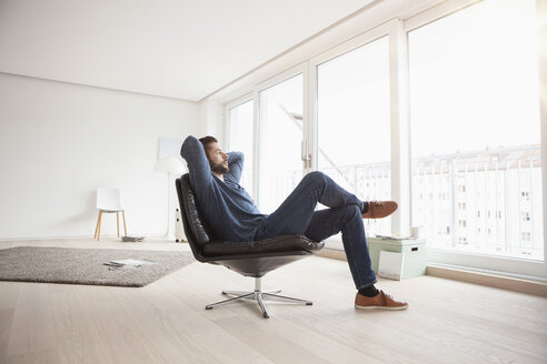Young man relaxing on leather chair in his living room - RBF002845