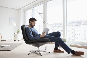 Young man sitting on leather chair in his living room using digital tablet - RBF002848