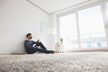 Young man sitting on the floor of living room looking through window - RBF002849