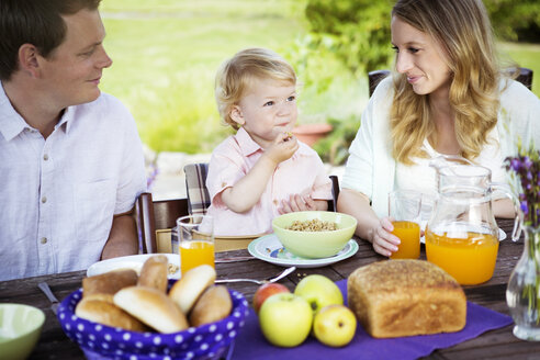Happy family sitting at breakfast table - GDF000741