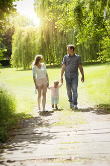 Parents walking with their little son in a park - GDF000751