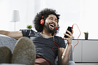 Laughing young man lying on couch at home listening music with headphones and smartphone - PDF001083