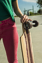 Young woman holding skateboard, close-up - UUF004666