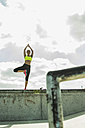 Young woman exercising yoga on a wall - UUF004662