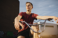 Young man with BMX bicycle looking away - GCF000089