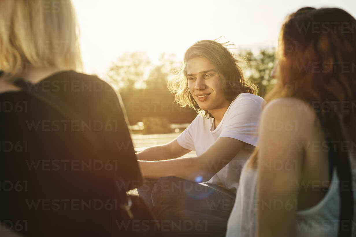 Friends sitting together outdoors at sunset - GCF000093 - Christian Gohdes/Westend61