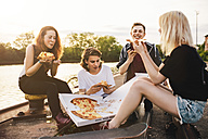 Friends sitting together outdoors sharing a pizza - GCF000098