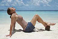 Maldives, woman relaxing on beach with feet on coconut - STKF001282