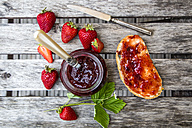 Strawberry jam in glass, strawberries and bread with jam on wood - SARF001858