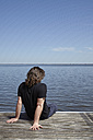 Back view of man sitting on jetty - MHCF000011