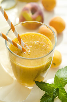 Peach-apricot-smoothie in a glass with drinking straw - ODF001136