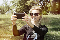 Smiling woman with sunglasses taking a selfie with her smartphone - CHPF000148