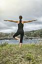 Spain, Gijon, woman doing yoga exercises - MGOF000282
