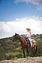 USA, Texas Hill Country, cowgirl sitting on horse - ABAF001815
