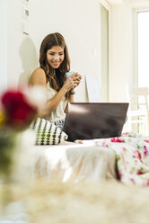 Relaxed young woman using laptop at home in bed - UUF004674